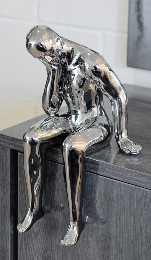 Ceramic thinking man sculpture in our showroom